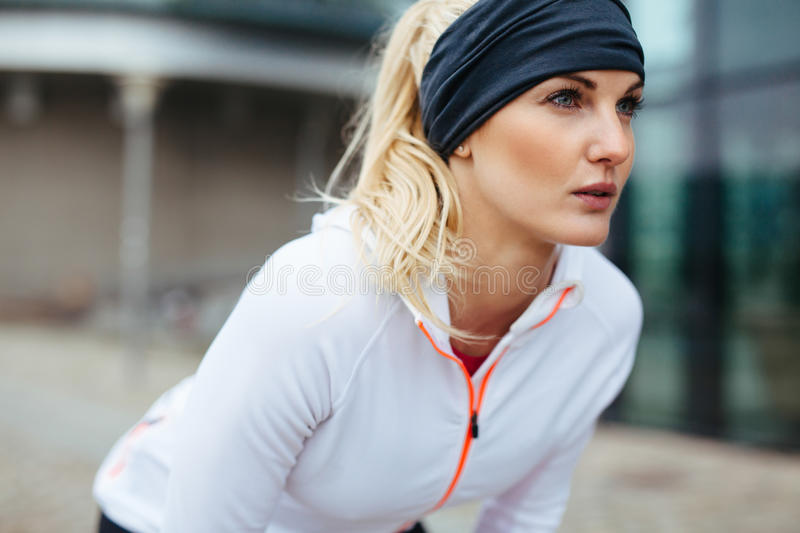 Sporty woman on outdoor workout looking confident. Young woman leaning over in sports gear. Determined sports woman looking forward for run stock photo