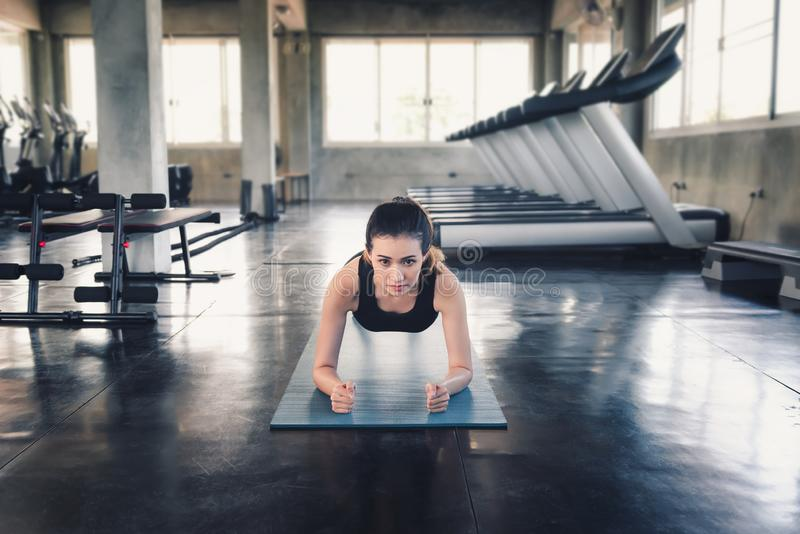 Sporty Woman is Planking Exercised or Yoga Practicing in Fitness Club,Portrait of Young Female is Working Out in Gym, Sport and royalty free stock photo