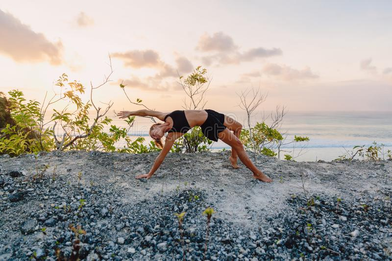 Sporty woman practice yoga at beach with sunset or sunrise stock image