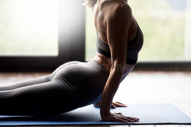 Young sporty woman doing upward facing dog exercise, close up stock images