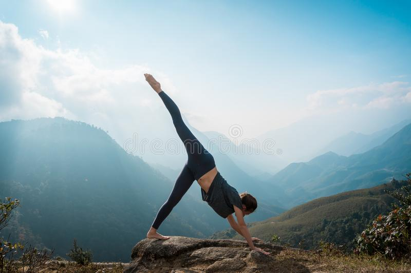 Sporty woman practicing yoga on mountain cliff at sunrise. Healthy lifestyle. Mountanious landscape stock images