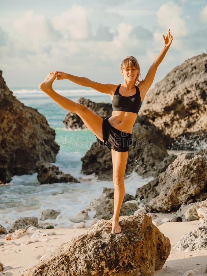 Sporty woman practicing yoga on the ocean beach. Yoga at sunset stock photo
