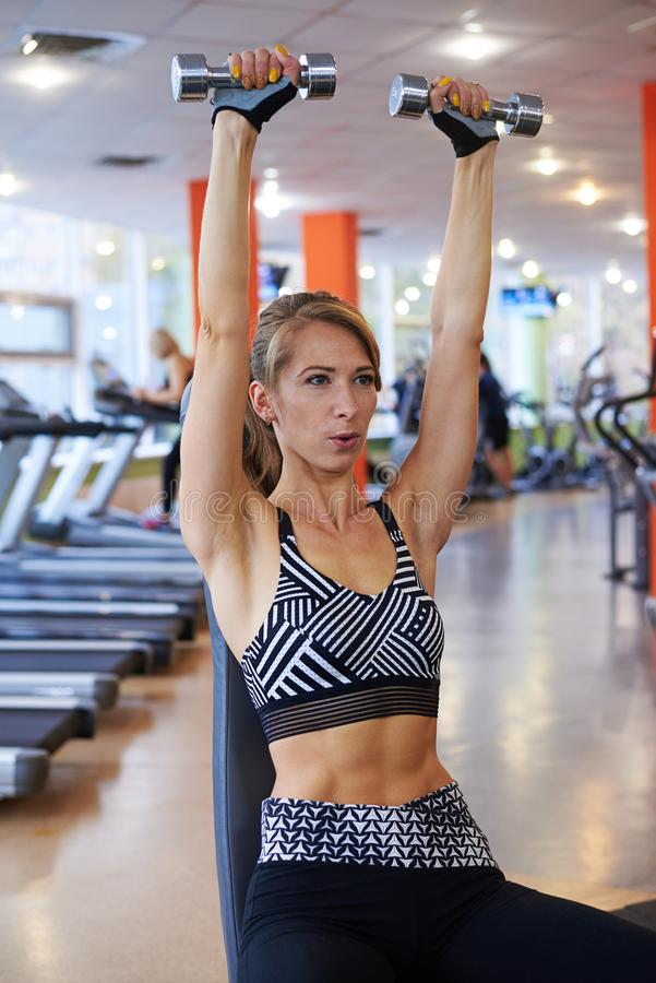 Sporty woman raising up dumbbells at gym stock image