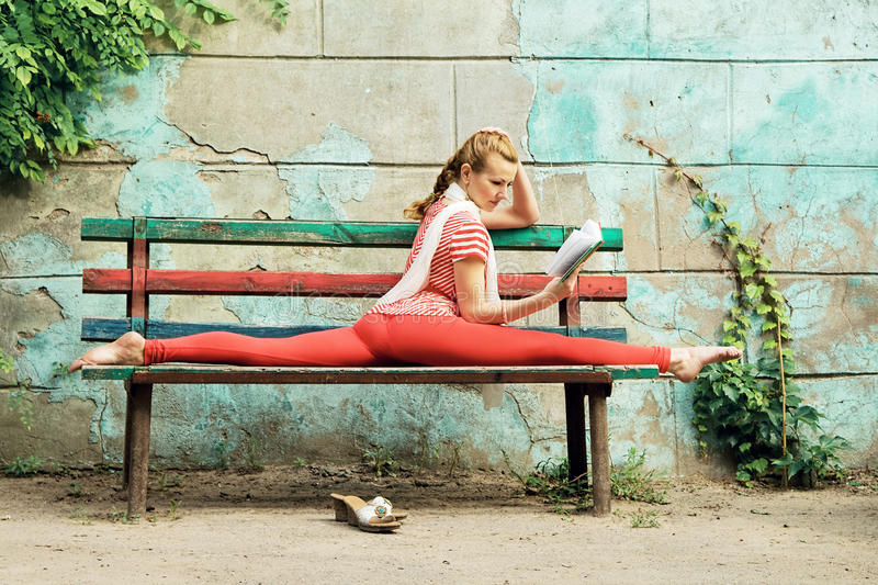 Sporty woman is reading a book and doing stretching exercise on. Beautiful sporty woman is reading a book and doing stretching exercise on bench in the street stock images