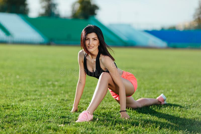 Sporty woman brunette runner in sport dress doing workout sessions on the field in a sports suit in the summer on a hot sunny day royalty free stock photos