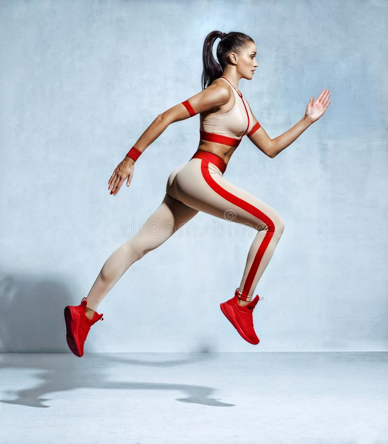 Sporty woman runner in fashionable sportswear on grey background royalty free stock photography