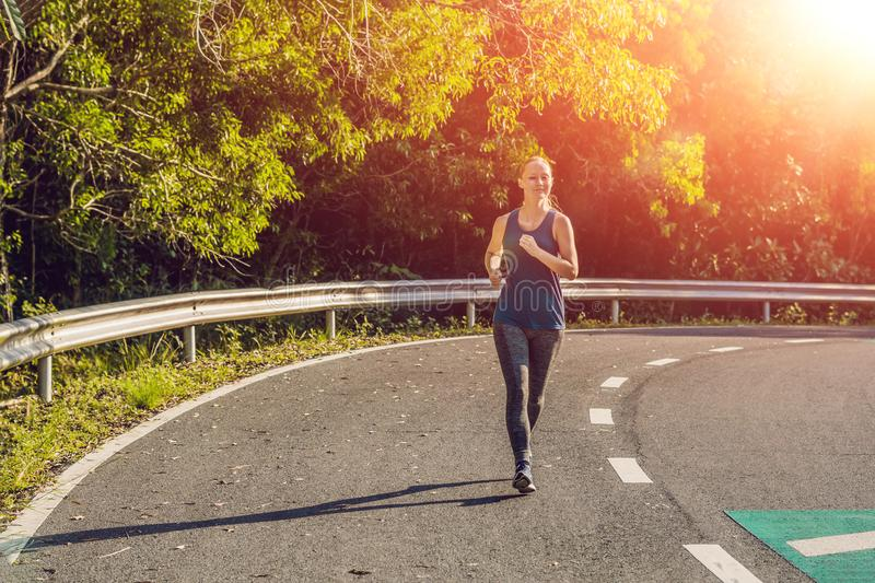 Sporty woman running on road at sunrise. Fitness and workout wellness concept.  stock image