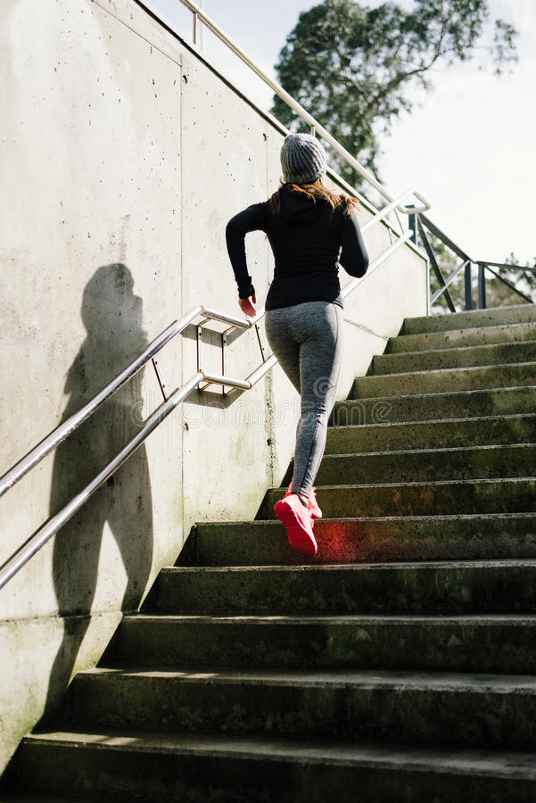 Sporty woman running upstairs in the city royalty free stock photography