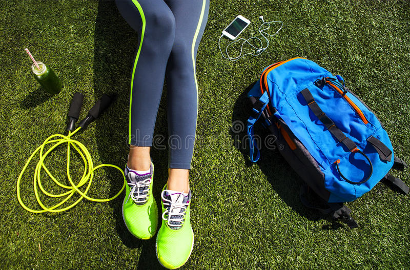 Sporty woman sitting on the green grass royalty free stock photo