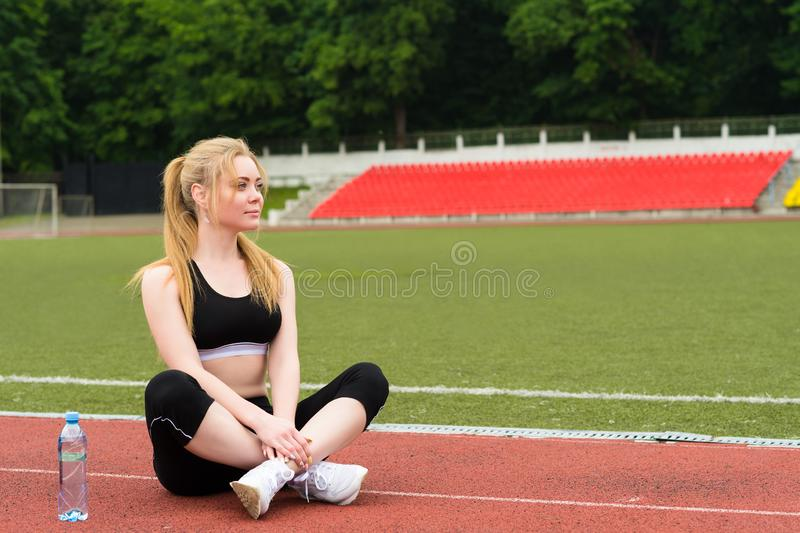 Sporty woman sitting on treadmill with bottle of water stock image