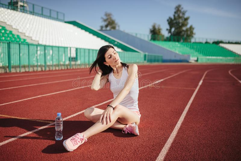 Sporty woman sitting on treadmill with bottle of water stock photos