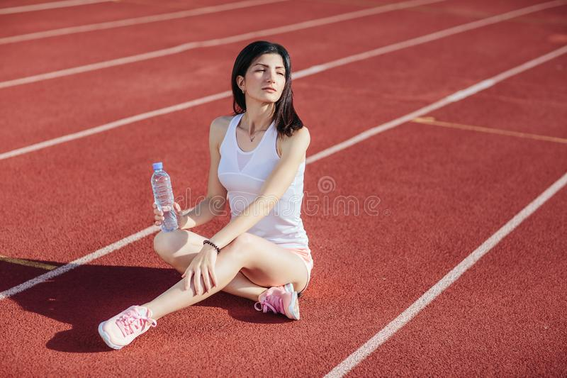 Sporty woman sitting on treadmill with bottle of water royalty free stock image