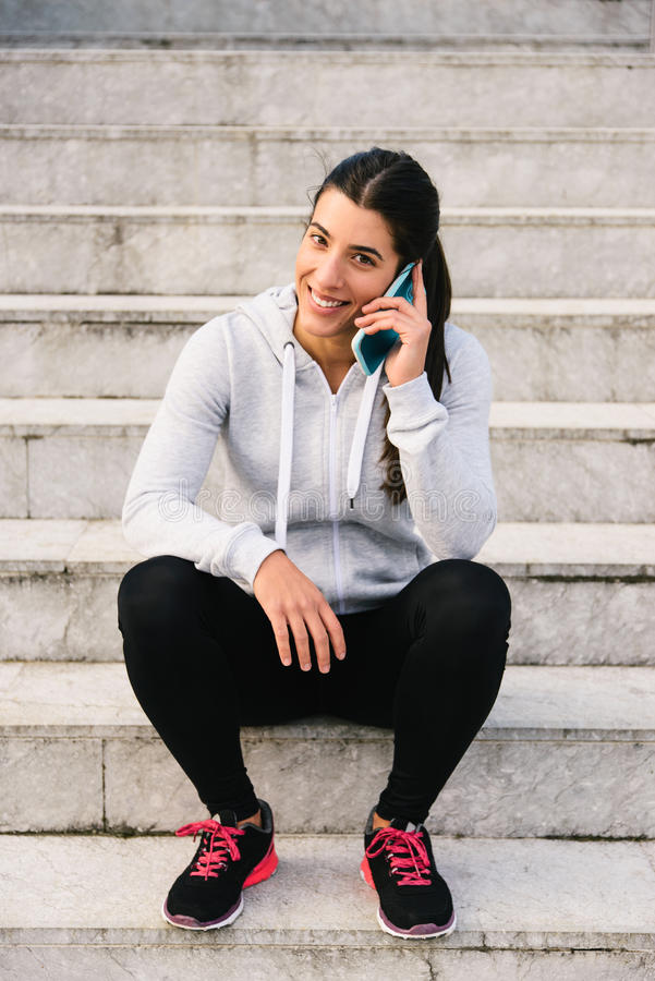 Sporty woman on smartphone call stock image