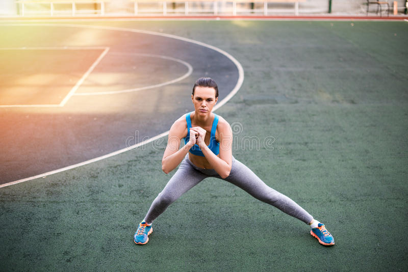 Sporty woman in sportswear exercising on stadium at sunset stock photography