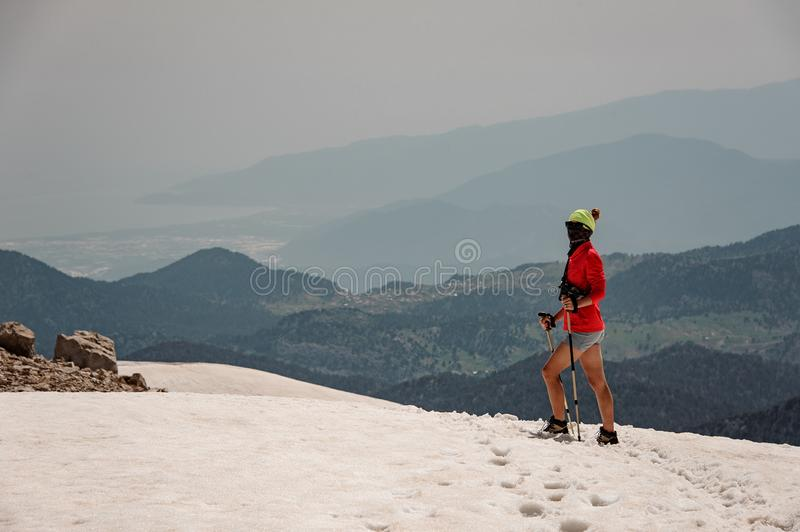 Sporty woman standing on the dirty snow on the Tahtali mountain with hiking sticks royalty free stock photos