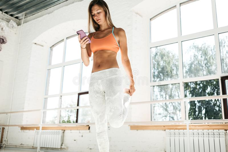Sporty woman stretching leg and hold smartphone in hand studies exercises in a sports fitness application. Healthy young girl warming up before workout and stock photography