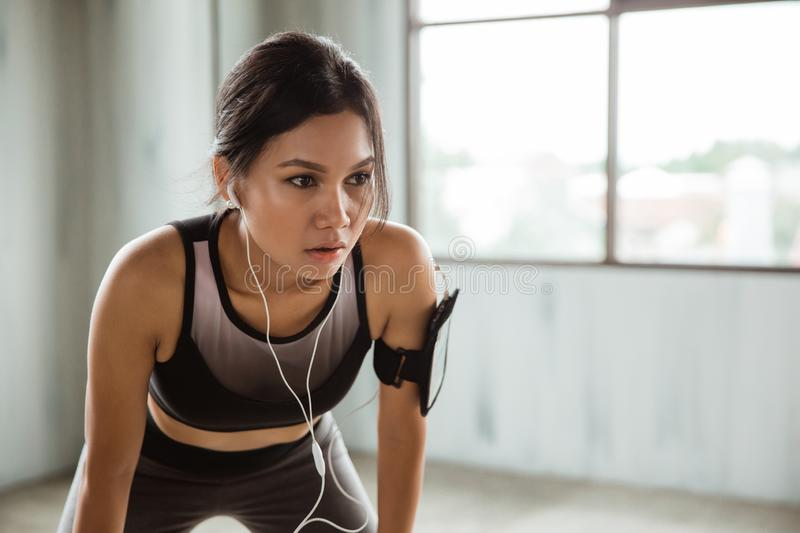 Sporty woman tired after doing hard exercises stock images