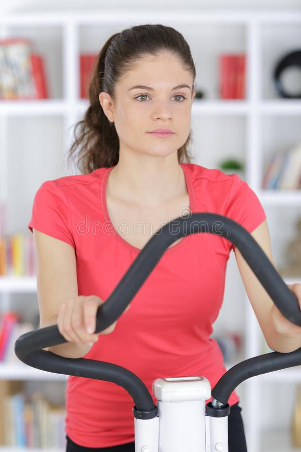 Sporty woman training on exercise bike at home royalty free stock photography