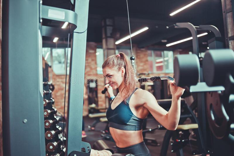 Sporty woman training her back with weight machine. In a gym, sport concept, fitness exercise stock photography