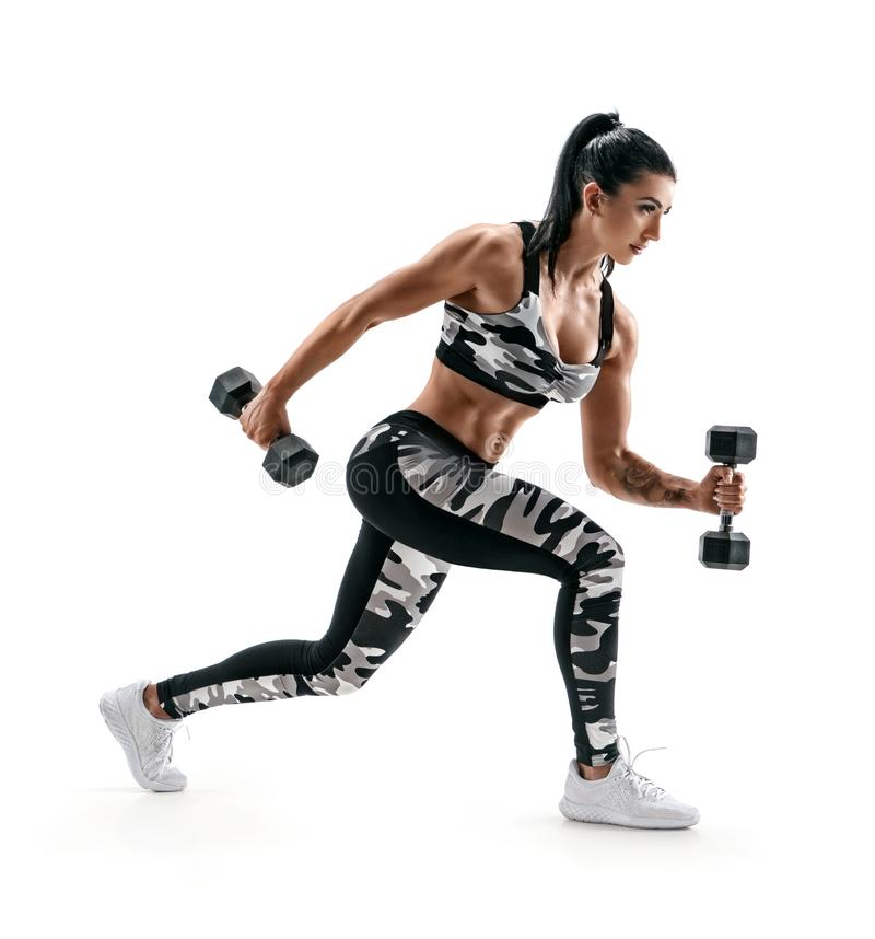 Sporty woman training muscles of hands and legs using a dumbbells. Photo of muscular latin woman in military sportswear isolated on white background. Strength stock photos
