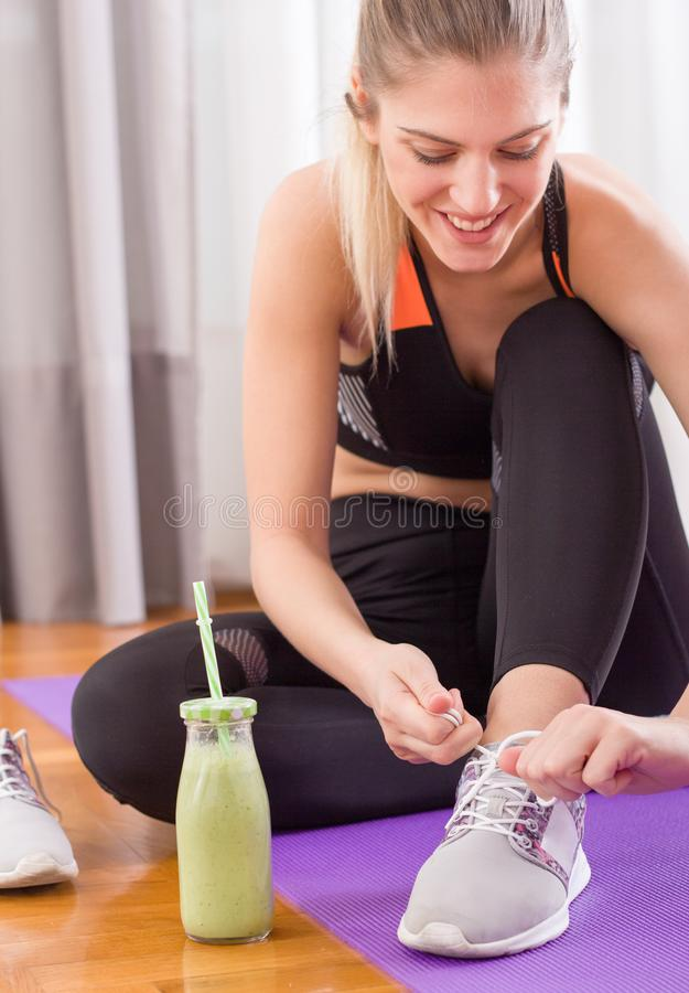 Sporty woman tying shoelaces on floor stock photography
