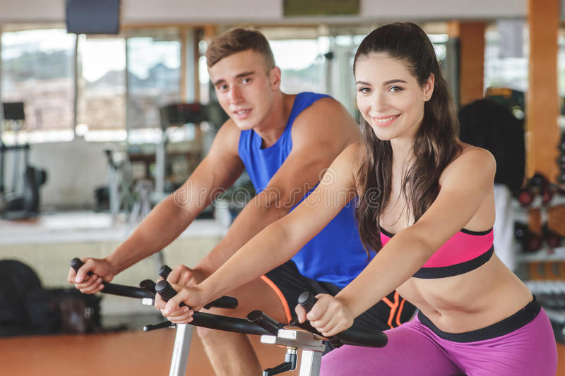 sporty woman using cycling exercise bike with her fitness partner royalty free stock photo