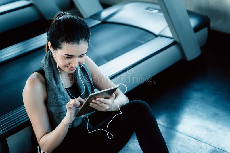 Sporty woman is using smartphone after treadmill exercising in fitness club., Portrait of asian woman listening to music with royalty free stock photography