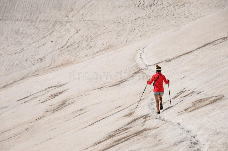 Sporty woman walk down on the dirty snow on the Tahtali mountain with hiking sticks stock photo