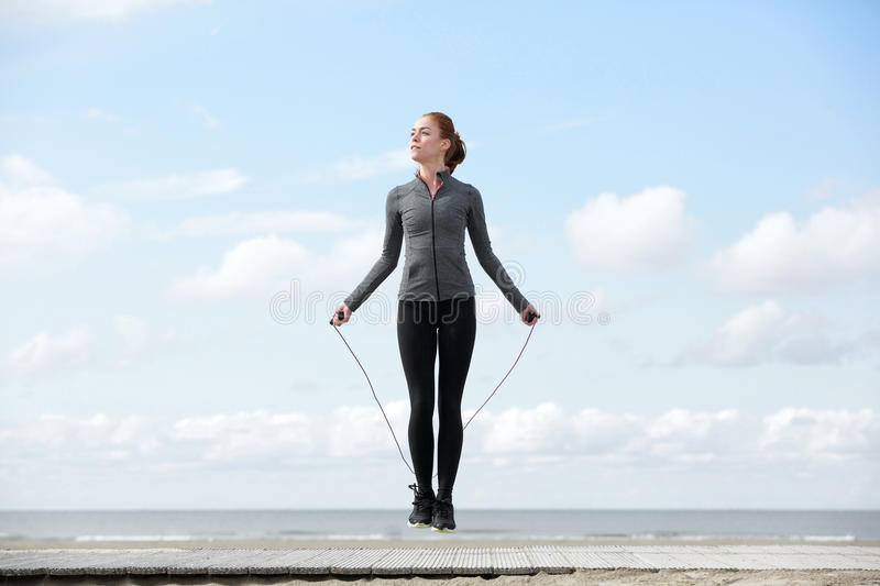 Sporty woman warming up with jump rope. Outdoors stock image