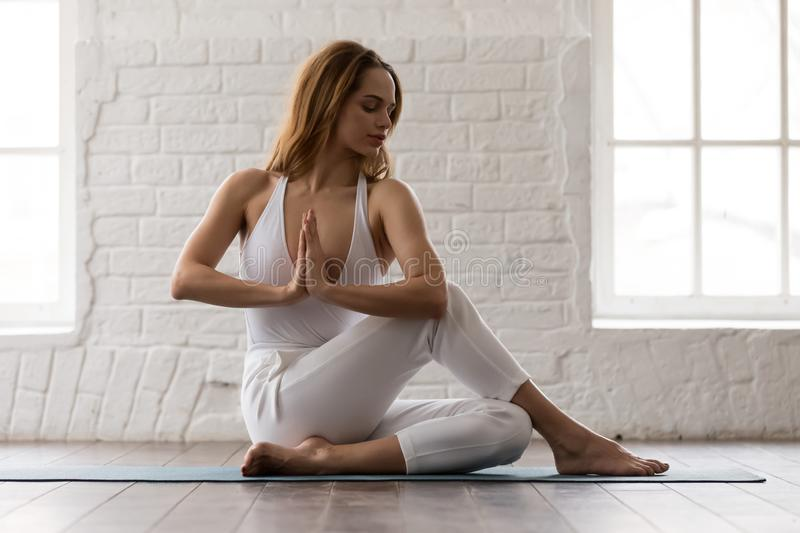 Sporty woman practicing yoga, sitting in Ardha Matsyendrasana pose stock photo