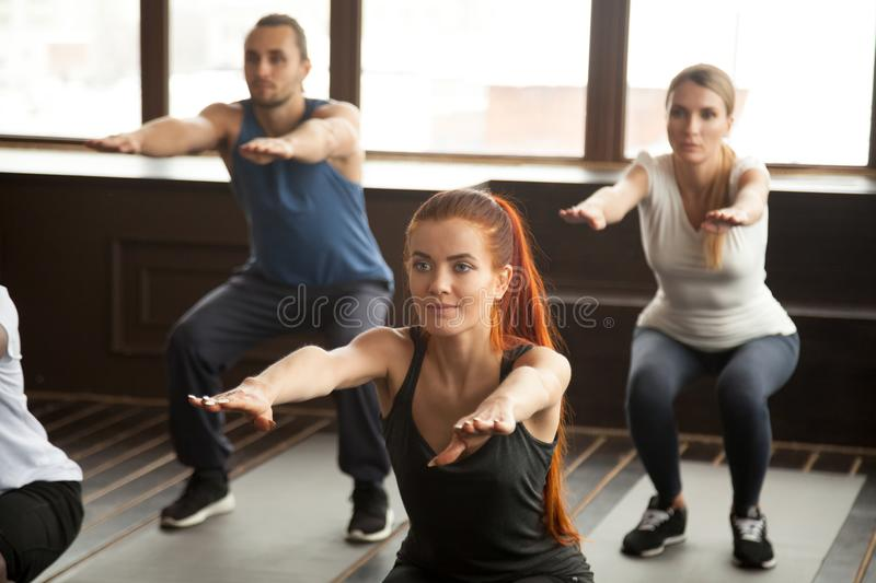 Sporty young people doing squat exercise at group fitness traini. Sporty women doing squat exercise at fitness training with young people, fit motivated group stock images