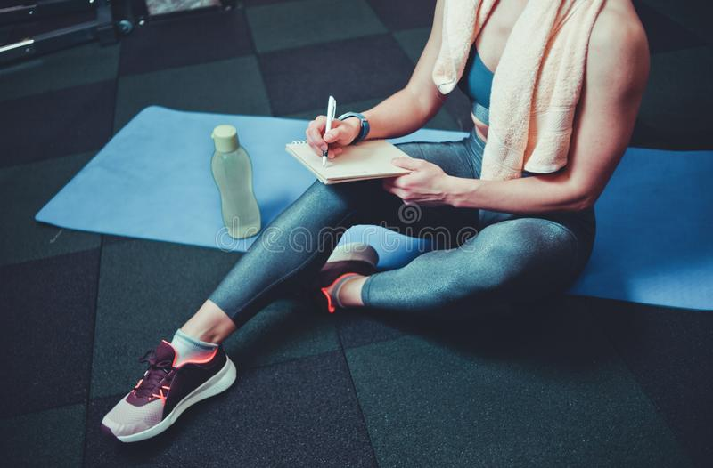 Sporty woman. Sporty women sits on a training mat and writes down future training plans for achieving great results in gym stock photo
