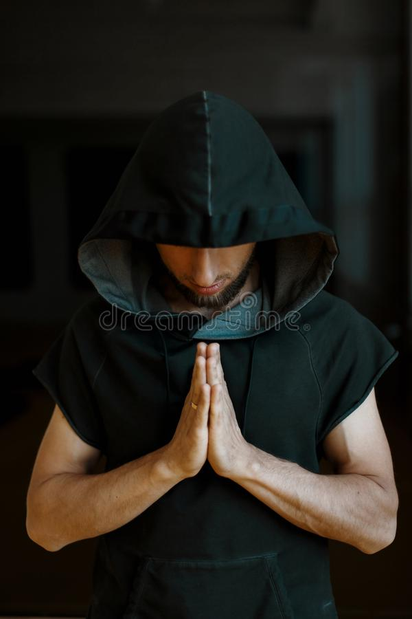 Sporty yoga man in a hood holds his hands on a dark background. Sporty yoga man in a hood holds his hands on a dark background royalty free stock images