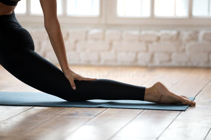 Sporty yogi woman practicing yoga, Horse rider exercise close up. Sporty yogi woman practicing yoga, doing Horse rider exercise, anjaneyasana pose, working out royalty free stock photography