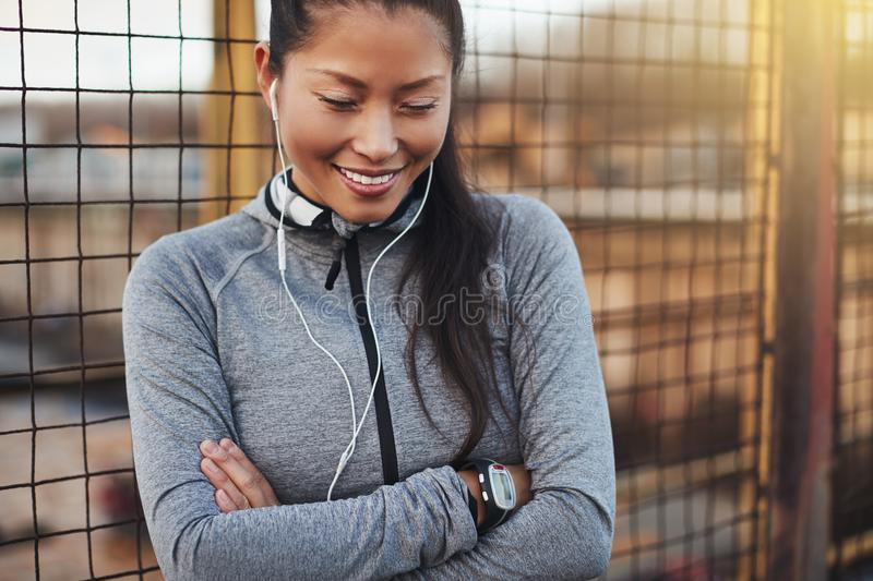 Sporty young Asian woman standing with her arms crossed outside stock photo