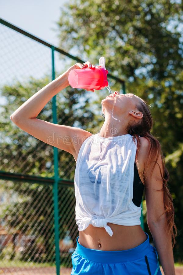 Sporty young blonde woman with a sporty bottle with cool illuminating water pours water on herself on sports field. Sporty young blonde woman with a sporty royalty free stock photos