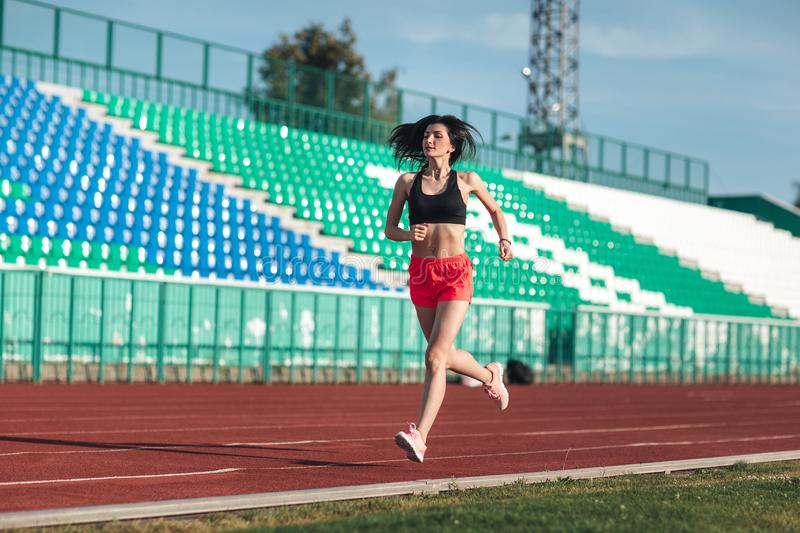 Sporty young brunette woman in pink shorts and tank top running at the stadium. Healthy active lifestyle. Summer sport activity royalty free stock image