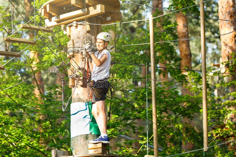 Sporty, young, cute boy in white t shirt spends his time in adventure rope park in helmet and safe equipment in the park. In the summer. Active lifestyle royalty free stock images