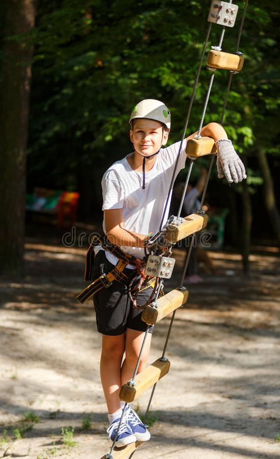 Sporty, young, cute boy in white t shirt spends his time in adventure rope park in helmet and safe equipment in the park. In the summer. Active lifestyle royalty free stock photos