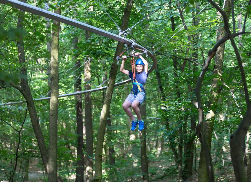 Sporty, young, cute boy in white t shirt spends his time in adventure rope park in helmet and safe equipment in the park. In the summer. Active lifestyle stock photography