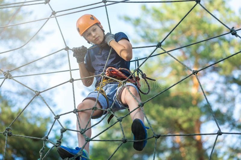 Sporty, young, cute boy in white t shirt spends his time in adventure rope park in helmet and safe equipment in the park. In the summer. Active lifestyle stock image