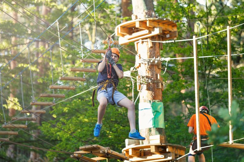 Sporty, young, cute boy in white t shirt spends his time in adventure rope park in helmet and safe equipment in the park stock photography