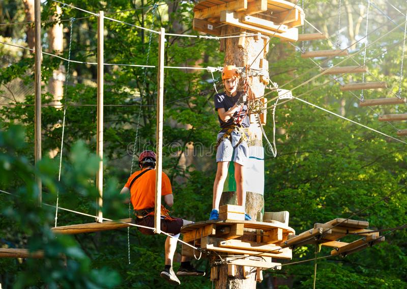 Sporty, young, cute boy in white t shirt spends his time in adventure rope park in helmet and safe equipment in the park. In the summer. Active lifestyle royalty free stock image