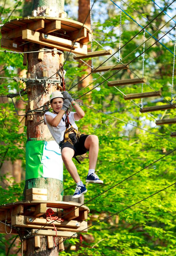 Sporty, young, cute boy in white t shirt spends his time in adventure rope park in helmet and safe equipment in the park. In the summer. Active lifestyle stock images