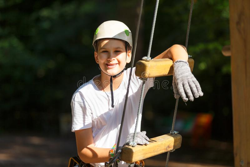 Sporty, young, cute boy in white t shirt spends his time in adventure rope park in helmet and safe equipment in the park. In the summer. Active lifestyle royalty free stock photo