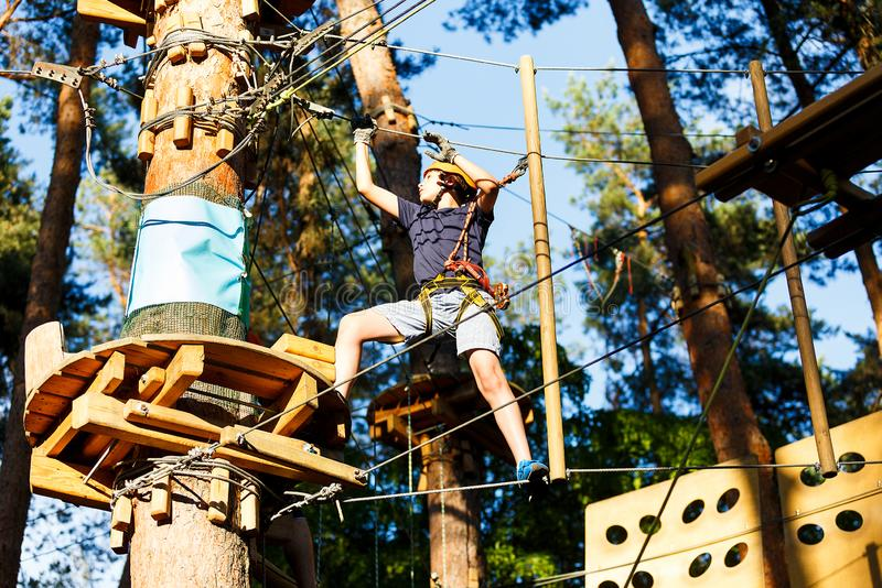 Sporty, young, cute boy in white t shirt spends his time in adventure rope park in helmet and safe equipment in the park. In the summer. Active lifestyle royalty free stock photography
