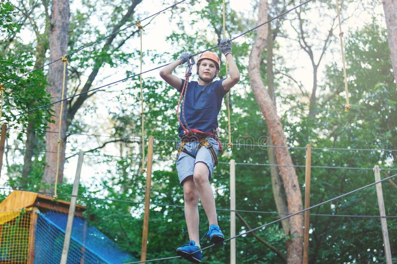 Sporty, young, cute boy in white t shirt spends his time in adventure rope park in helmet and safe equipment in the park. In the summer. Active lifestyle stock photo