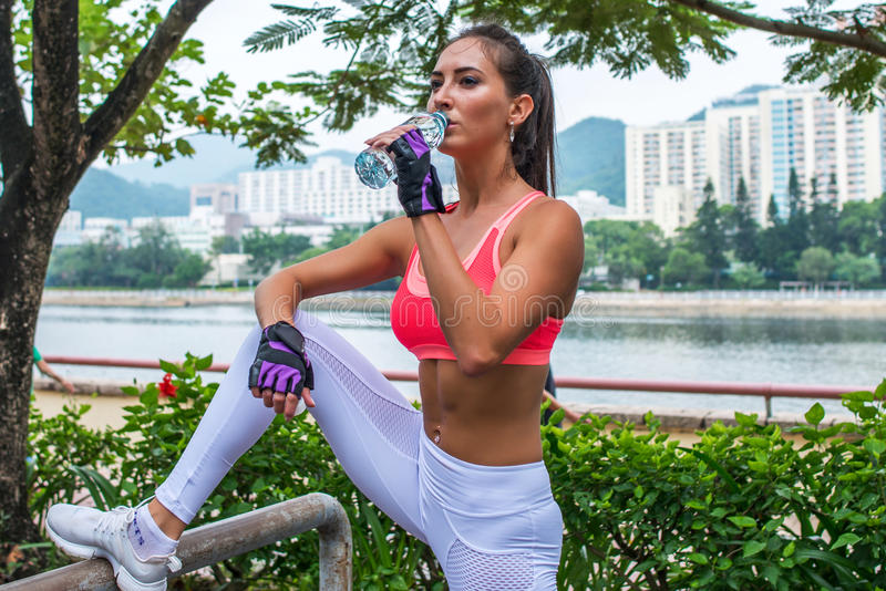 Sporty young female athlete taking a break after exercising or running, standing and drinking water from bottle in park royalty free stock photos