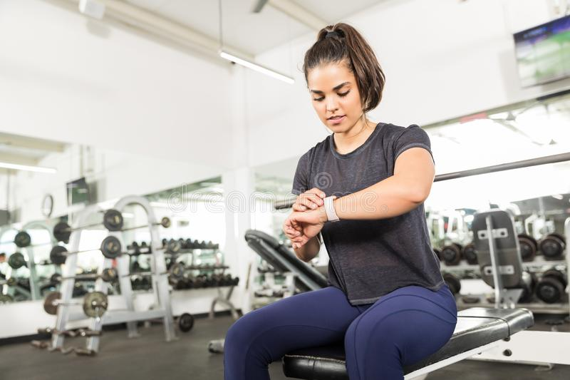Sporty Female Checking Fitness Activity On Smart Watch In Gym stock photo