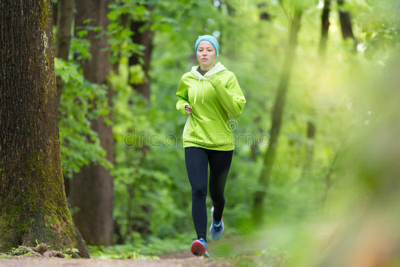 Sporty young female runner in the forest. Sporty young female runner in forest. Running woman. Female runner during outdoor workout in nature. Fitness model stock photo